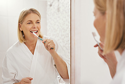Woman brushing teeth before oral hygiene checkup at Cooley Smiles