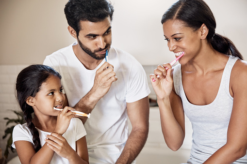Family brushing teeth before oral hygiene checkup at Cooley Smiles