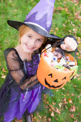 A little girl in a witch costume holding up a bag of candy!
